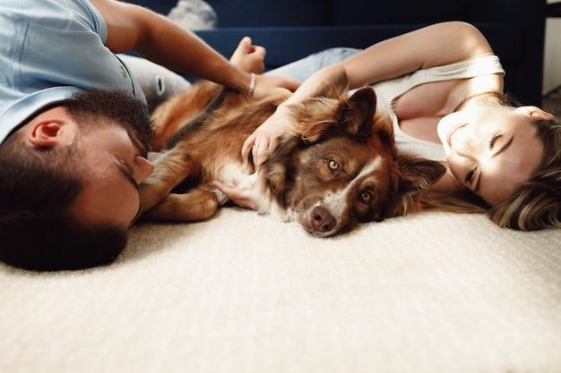 Gelukkige paar liggend op de vloer met hun hond knuffelen met huisdier
