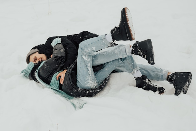 Gelukkige paar liggend op sneeuw lachen en knuffelen