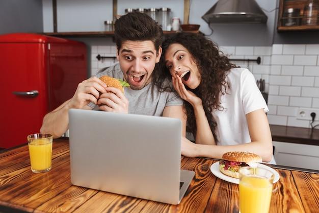 Gelukkige paar man en vrouw kijken naar laptop op tafel terwijl ze thuis hamburger eten in de keuken