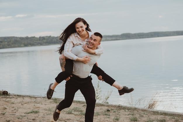 Gelukkige paar meisje en jongen plezier op het strand aan de rivier in de zomer. de foto is wazig door beweging en korte sluitertijd