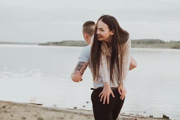Gelukkige paar meisje en jongen plezier op het strand aan de rivier in de zomer