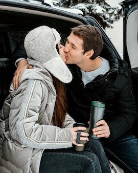 Gelukkige paar met een warm drankje in de kofferbak van de auto en kussen tijdens een roadtrip