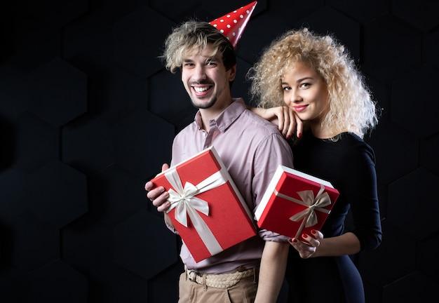 Gelukkige paar met geschenkdozen, camera kijken met een glimlach. viering en romantisch concept.