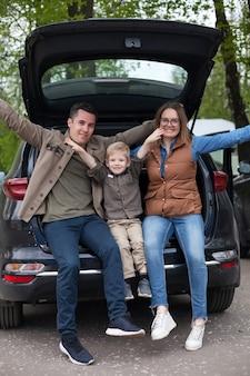 Gelukkige paar met hun jonge zoon in open kofferbak van off-road voertuig op parkeerplaats