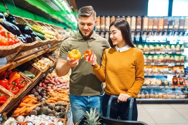 Gelukkige paar met mand in de supermarkt