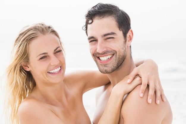 Gelukkige paar omarmen op het strand