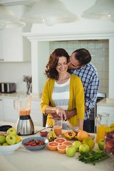 Gelukkige paar omarmen tijdens het voorbereiden van smoothie in keuken