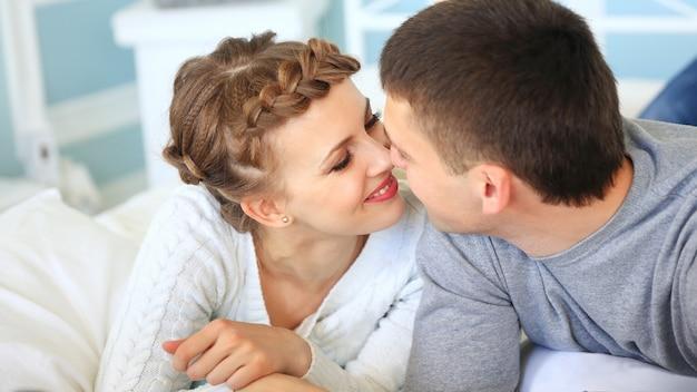 Gelukkige paar op een slaapbank in de woonkamer, kijken naar elkaar