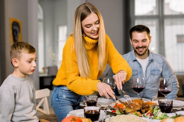 Gelukkige paar ouders en hun zoontje aan feestelijke tafel zitten en gaan geroosterde kalkoen eten. gelukkige familie die heerlijk diner hebben samen thuis terwijl moeder scherp turkije