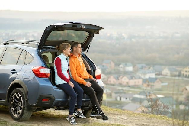 Gelukkige paar permanent samen in de buurt van een auto met open kofferbak genieten van uitzicht op het landschap van de natuur. man en vrouw die op de bagageruimte van het gezinsvoertuig leunen. weekend reizen en vakantie concept.
