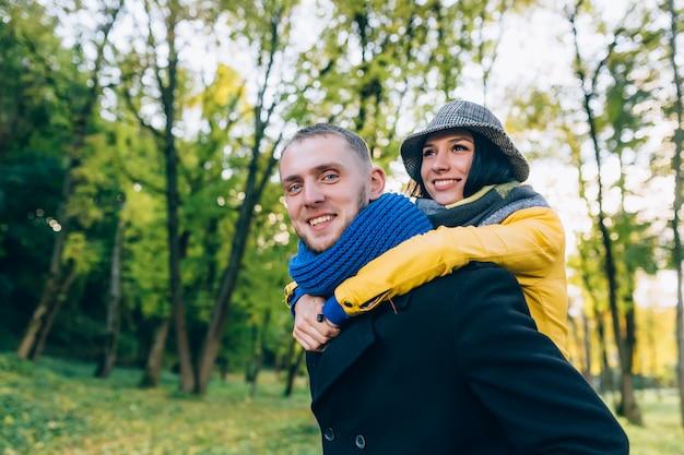 Gelukkige paar plezier in herfst park. gele bomen en bladeren. lachende man en vrouw buiten. vrijheid concept.