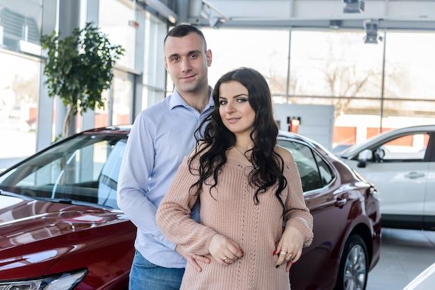 Gelukkige paar poseren met nieuwe auto's in showroom