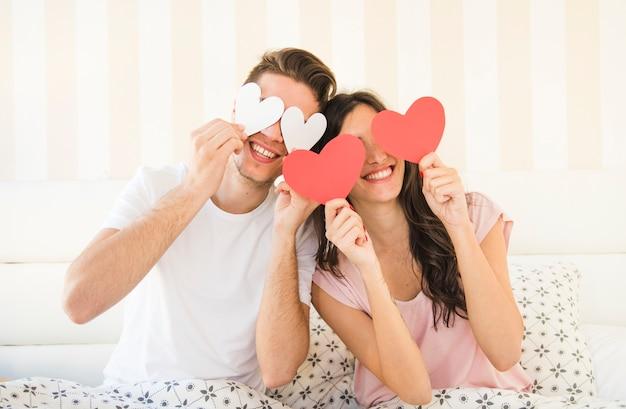 Gelukkige paar poseren met papier hart