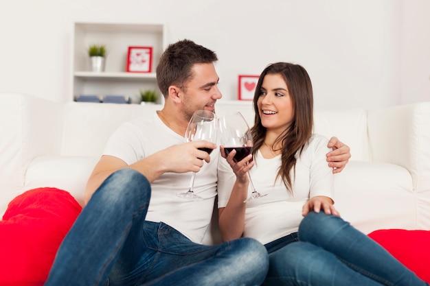 Gelukkige paar romantische tijd doorbrengen met rode wijn thuis