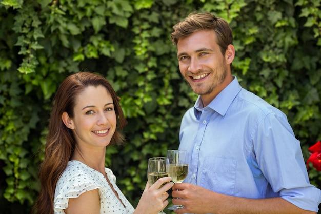 Gelukkige paar roosterende wijnglazen bij voortuin