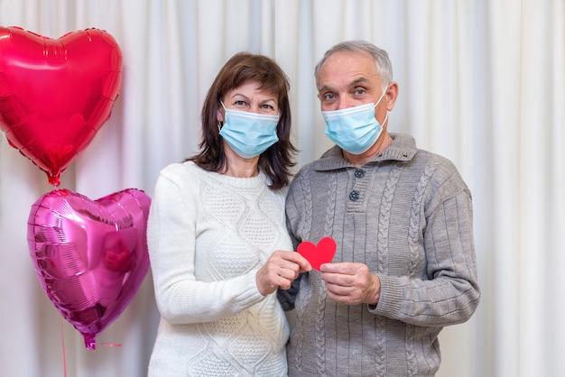 Gelukkige paar senioren vieren valentijnsdag in masker.