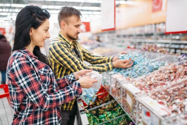 Gelukkige paar snoep en suikergoed in supermarkt kopen. mannelijke en vrouwelijke klanten bij het winkelen met het gezin. man en vrouw die voedsel kopen