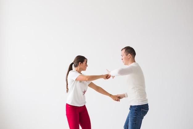 Gelukkige paar sociale dans dansen op lichte muur