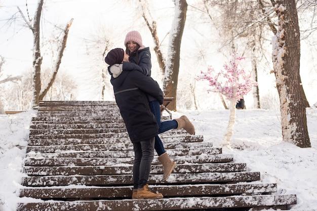 Gelukkige paar speels samen tijdens wintervakantie vakantie buiten in snowpark
