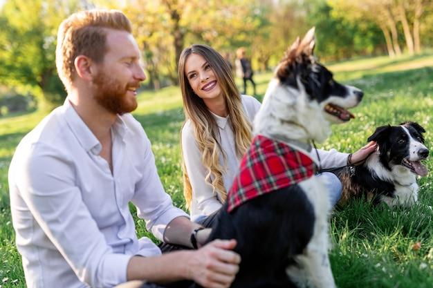 Gelukkige paar spelen met hond in het park buiten. mensen, huisdierenconcept