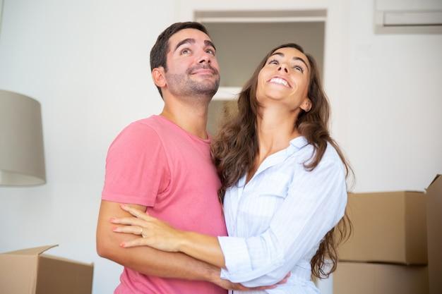 Gelukkige paar staande onder kartonnen dozen en knuffelen, uitkijkend over hun nieuwe appartement