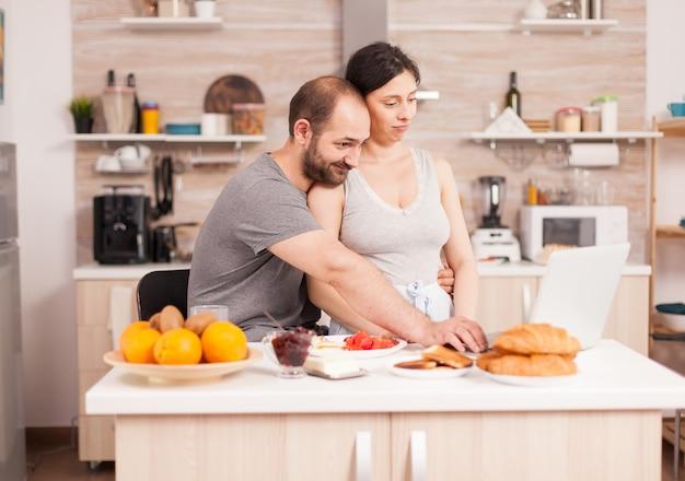 Gelukkige paar surfen op internet met behulp van laptop tijdens het ontbijt in de keuken. getrouwde man en vrouw in pyjama met behulp van internet web online moderne technologie, glimlachend en gelukkig in de ochtend. lezen nee