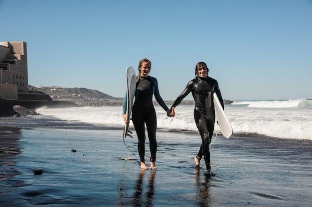 Gelukkige paar surfers wandelen en lachen langs de kust met zwart zand op zonnige dag