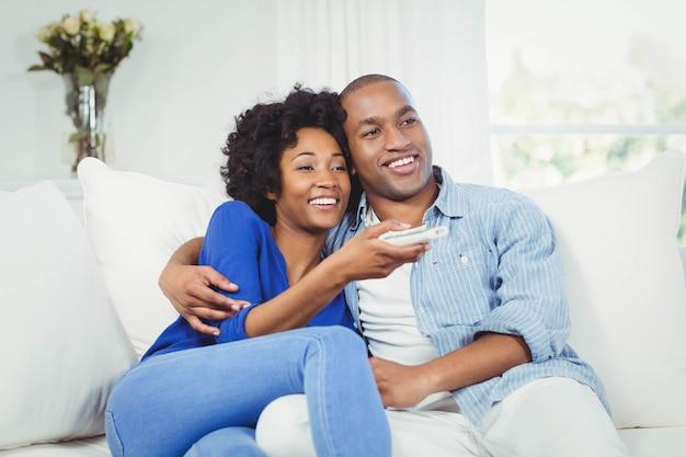 Gelukkige paar televisie kijken op de bank in de woonkamer