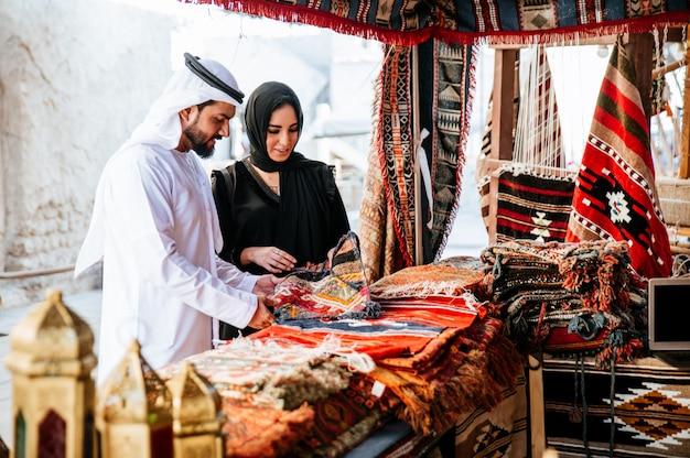 Gelukkige paar tijd doorbrengen in dubai. man en vrouw, gekleed in traditionele kleding maken winkelen in de oude stad