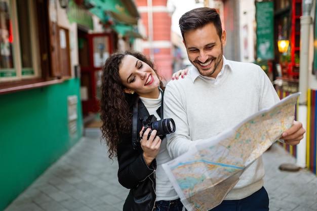 Gelukkige paar toeristen sightseeing stad met kaart. mensen, reizen, leuk concept