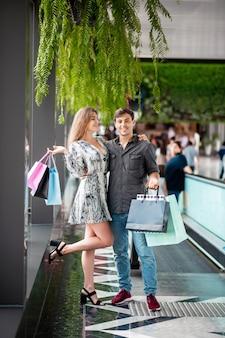 Gelukkige paar van een jonge man en een lachend meisje knuffelen na een grote winkelen, met een pakket met aankopen in hun handen. druk emoties uit van vreugde, tevredenheid. grote aankopen. dag van kortingen.