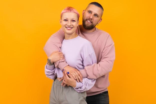 Gelukkige paar van man en vrouw met gekleurd haar en piercings gekleed in casual roze kleding staan op geel