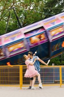Gelukkige paar verliefd genieten van elkaar in een pretpark. een jongen en een meisje die suikerspin eten en lachen