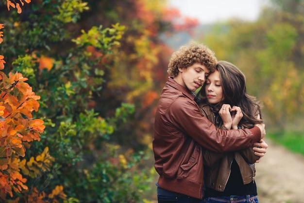 Gelukkige paar verliefd in de herfst. man met gekruld haar en besnorde mannen en vrouw met rood haar in leren jassen en spijkerbroeken omhelzen elkaar teder