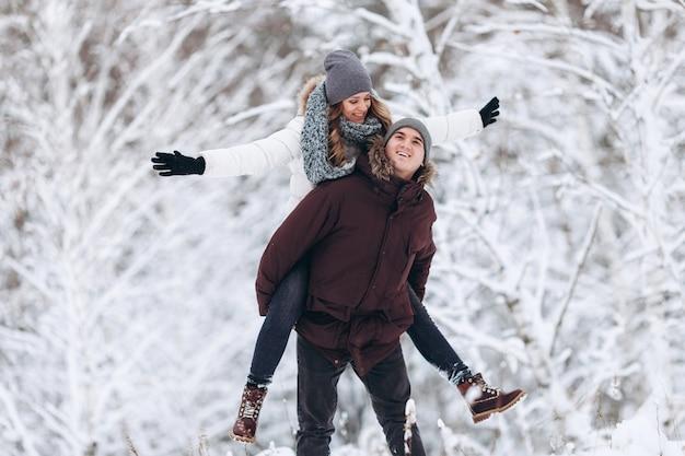 Gelukkige paar verliefd in de winter in een besneeuwd bos, een meisje rijdt op de rug van haar geliefde man spelen en glimlachen