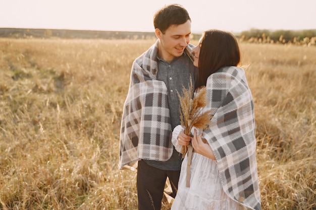 Gelukkige paar verliefd in tarweveld bij zonsondergang