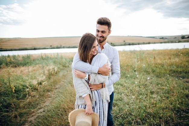 Gelukkige paar verliefd knuffelen, zoenen en lachend tegen de hemel in het veld. hoed in meisjeshand