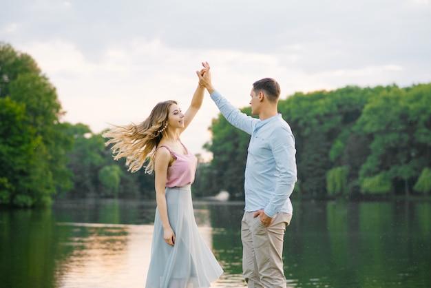 Gelukkige paar verliefd man en meisje dansen op de oever van een prachtig meer. zacht en mooi paar pasgetrouwden. valentijnsdag