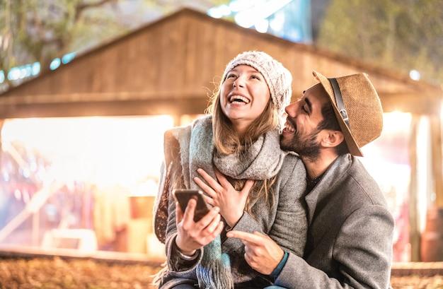 Gelukkige paar verliefd met plezier met mobiele slimme telefoon op wintertijd