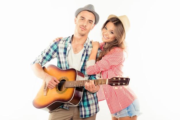 Gelukkige paar verliefd op hoeden en gitaar