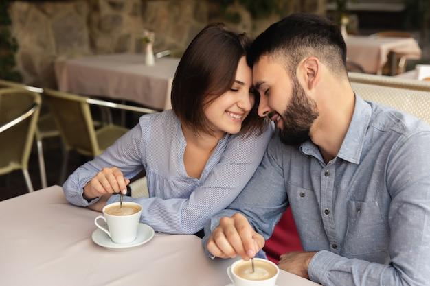 Gelukkige paar verliefd thuis blijven. man en vrouw die bij elkaar glimlachen alvorens binnen koffie te drinken