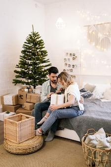 Gelukkige paar verliefd zittend op het bed geschenken te geven bij de kerstboom in een gezellig huis
