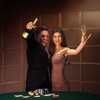 Gelukkige paar vieren overwinning in poker met champagne. afhankelijk van het concept van gokken en casino's