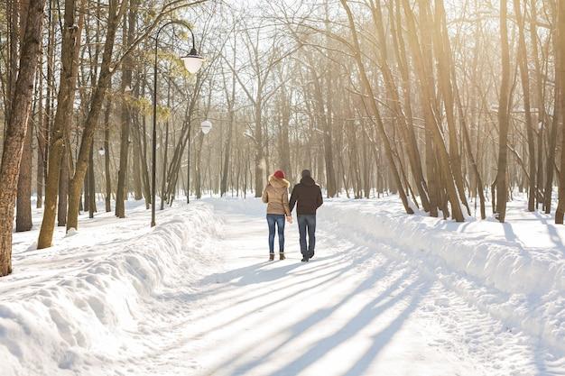 Gelukkige paar wandelen door een besneeuwd bos in de winter.