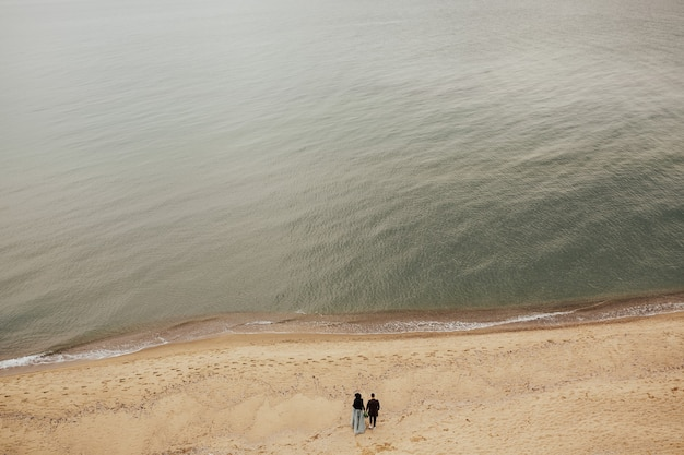 Gelukkige paar wandelen langs het strand van veraf.