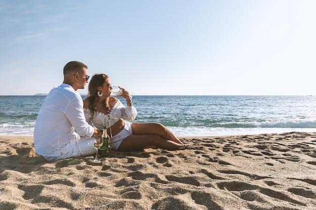 Gelukkige paar zitplaatsen met champagne op het strand.