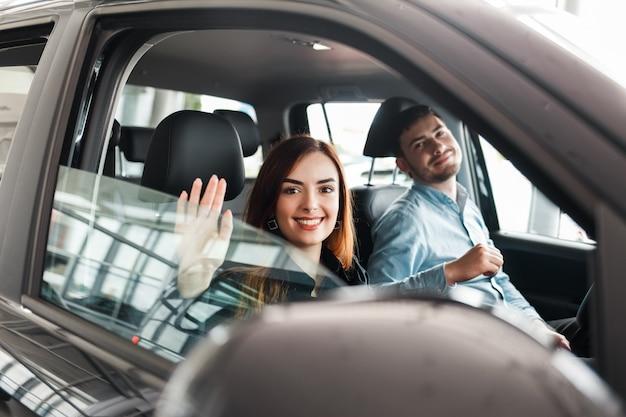 Gelukkige paar zitten in hun nieuwe auto