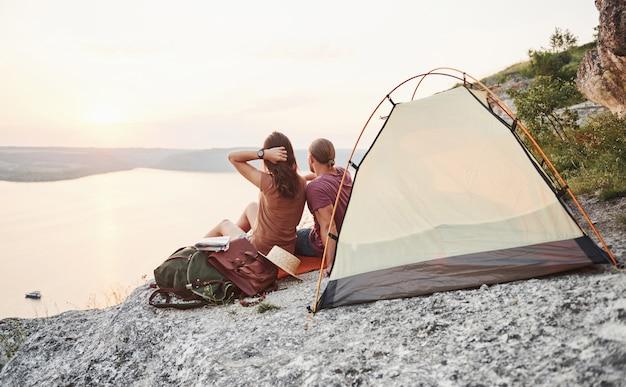 Gelukkige paar zitten in tent met uitzicht op meer tijdens wandeltocht. avontuur vakanties concept Premium Foto