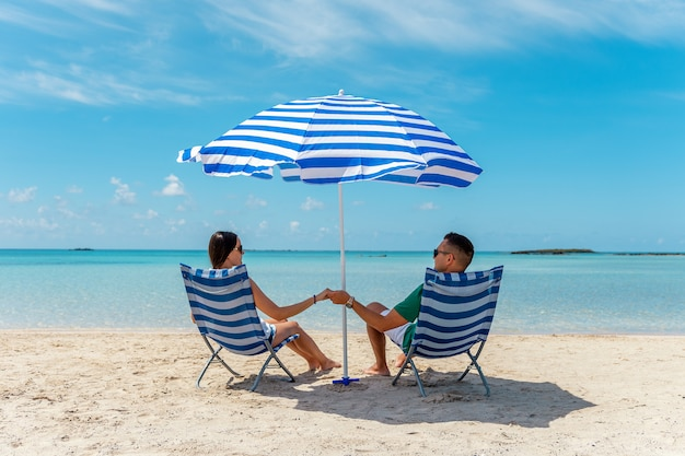 Gelukkige paar zittend in stoelen onder parasol op een tropisch strand