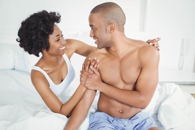 Gelukkige paar zittend op bed en praten